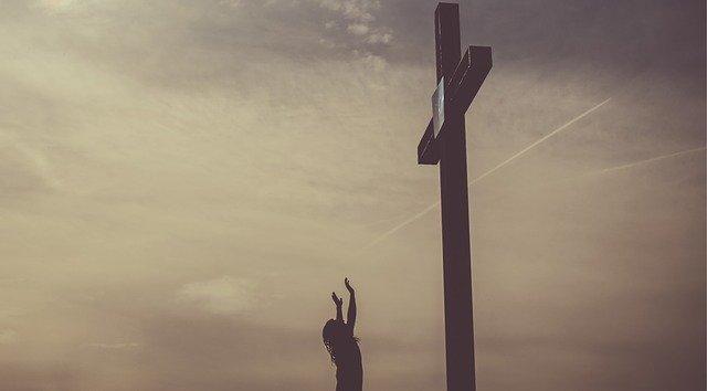 Kobieta modli się pod krzyżem
