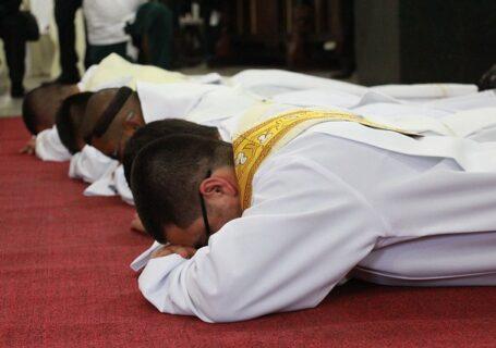Ksiądz modlący się krzyżem